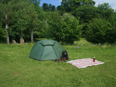 Hikers' tent on a traditional grass camping pitch at Tyn Cornel