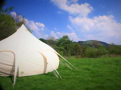 Lotus Belle Tent (a distinctive type of glamping tent) with the view from Tyn Cornel Camping