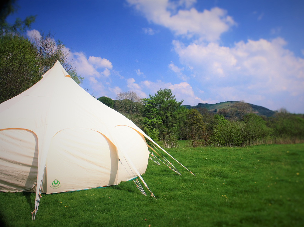 Lotus Belle Tent (a distinctive type of bell tent used for glamping) with the view from Tyn Cornel Camping