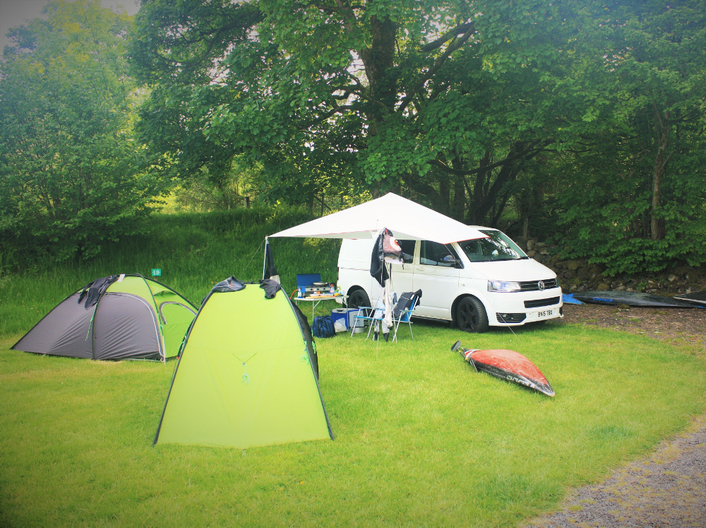 Tents, slalom kayaks and a VW van on a grass electric hook up pitch at Tyn Cornel