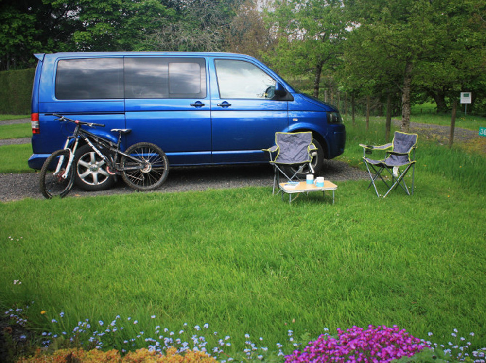 VW campervan and a mountain bike on a hardstanding touring pitch with a grassy area for picnics at Tyn Cornel Camping