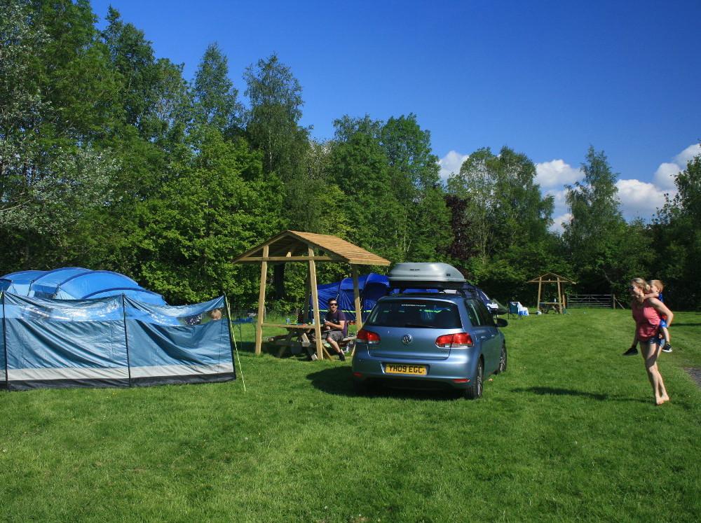 Family enjoying a traditional grass camping pitch at Tyn Cornel Campsite near Bala