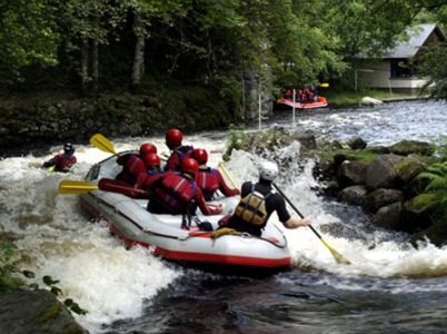 A group enjoying white water rafting past the national Whitewater Centre, Snowdonia National Park