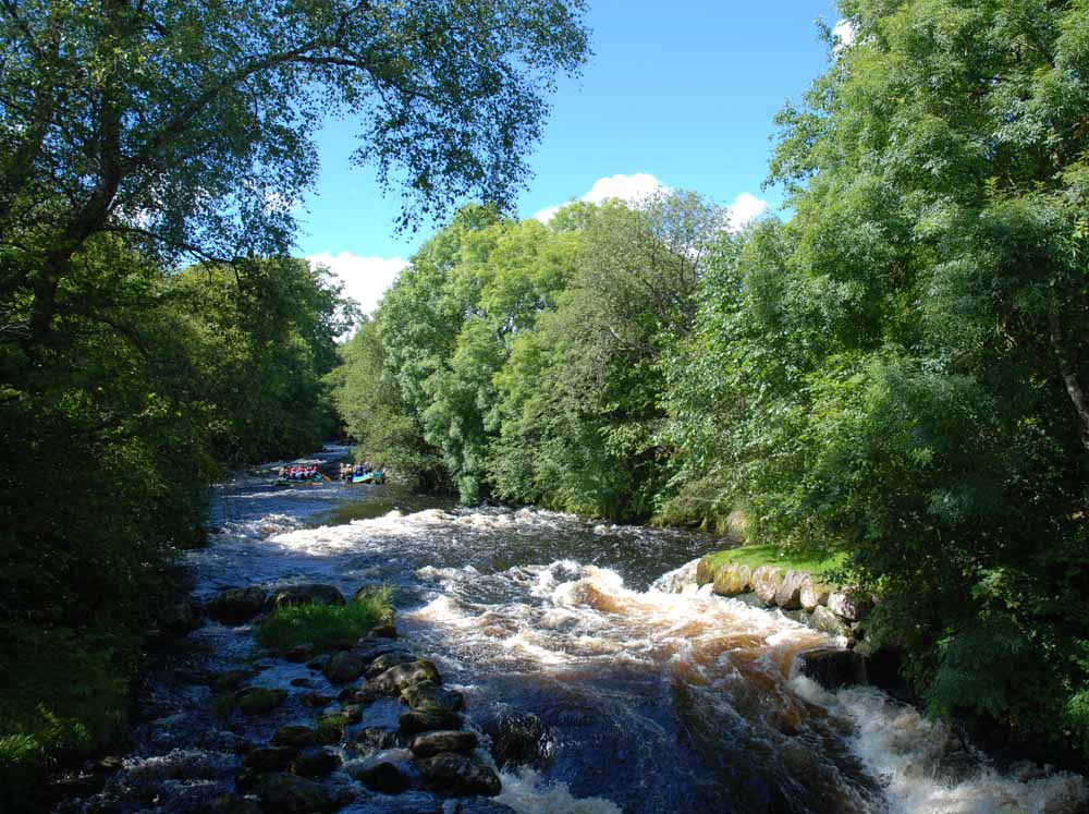 Blues skies above the stunning River Tryweryn and white water rafting next door to Tyn Cornel Camping